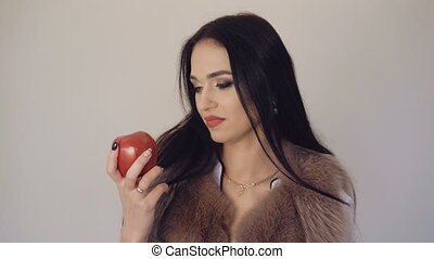 Smart girl eating a big, dark red apple, smiling and flirting to camera 4K