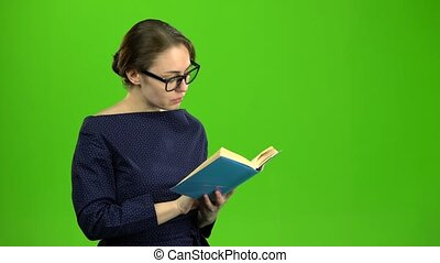 Smart girl is reading a book. Green screen - Smart girl in...