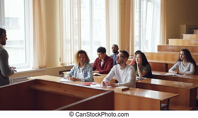 Smart guy student is raising hand and talking to professor while fellow students are listening to them and smiling. Pupil and teacher relations concept.