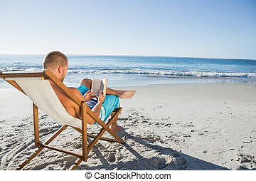 Smart handsome man reading a book on the beach