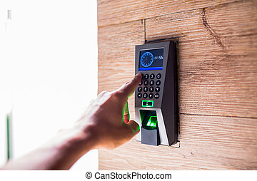 Smart home keyboard password entrance. Human hand pressing the security code combination to unlock the door.