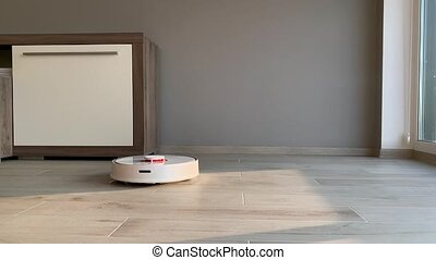 Smart House. Vacuum cleaner robot runs on wood floor in a...