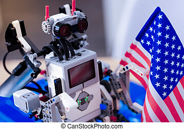 Smart innovative robot looking at the US flag