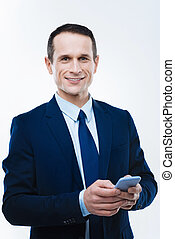 Smart intelligent businessman holding his smartphone