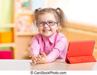Smart kid in spectacles with tablet PC in her room