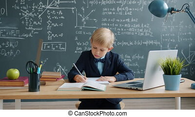 Smart little boy writing at desk in class, formulas are on chalkboard in background