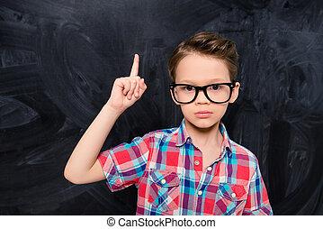 Smart little school boy in glasses having an idea