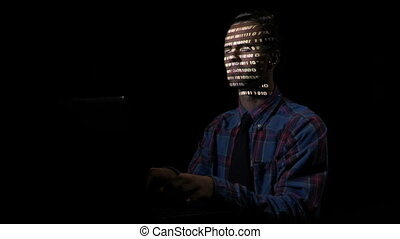 Smart male computer programmer attacking cyber security servers from his underground hideout while the screen reflects binary code on his face