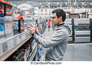smart male customer buying car battery n the car supermarket