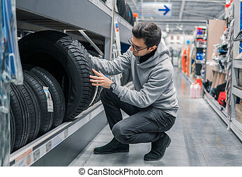 Smart male customer choosing new tires in the supermarket