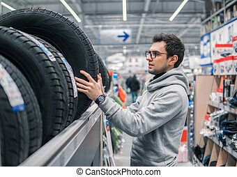 Smart male customer choosing new tires