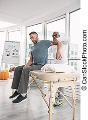 Smart male therapist holding his patients arm
