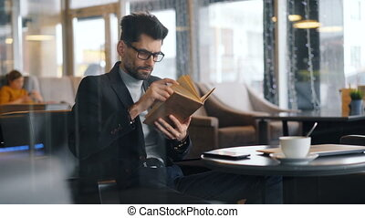 Smart man businessperson reading book in cafe focused on...