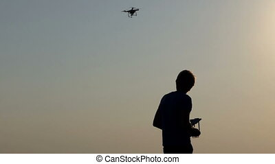 Smart man controls his flying drone with panel at sunset in slo-mo