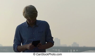 Smart Man Works at His Smartphone And Thinks Outdoors at the...