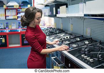 female housewife customer choosing large gas stove
