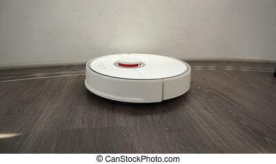 Smart modern vacuum cleaner cleans the laminate wood floor...