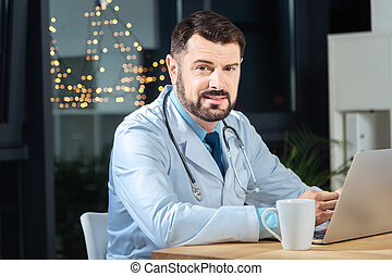 Smart nice doctor looking at you