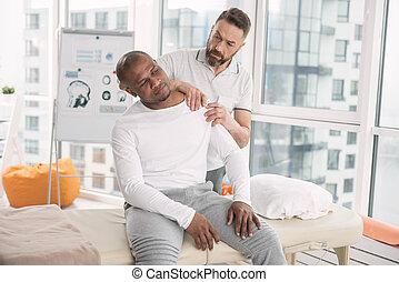 Smart nice man touching his patients shoulder