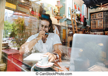 Smart nice man working from the cafe