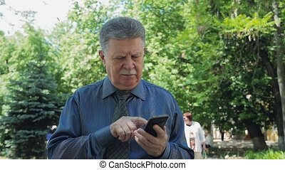 Smart old man typing a message on his phone while going in a...