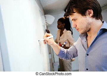 Smart people writing on whiteboard
