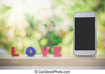Smart phone and love alphabet on wood with bokeh background,
