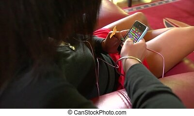 smart phone game - Teenaged girl playing a video game on her...