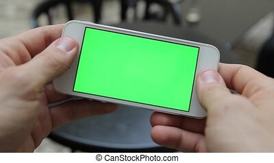 Smart Phone Held by Hand. Green screen Chroma Key Tracking Motion Vertical. Person Sitting Telephone on the Hands Rotate Animation