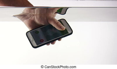 Smart phone in hand submerged underwater starts ringing with...