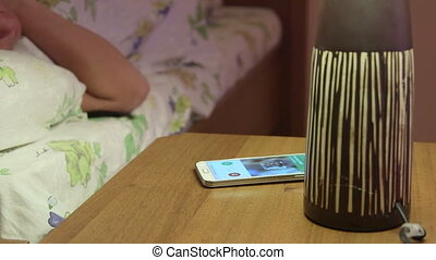 Smart phone incoming call on bedside table at night