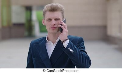Smart phone man calling on mobile phone at night in city. Handsome young business man talking on smartphone smiling happy wearing suit jacket outdoors. Urban male professional in his 20s