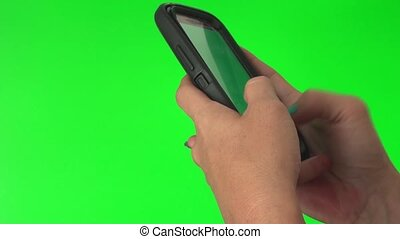 Hands using a smart phone for texting on a green screen