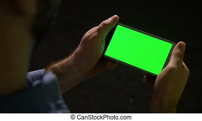 Smart phone with green screen held in hand by man making swipe and zoom gestures