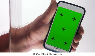 Smart phone with green screen in hand dipping into the water