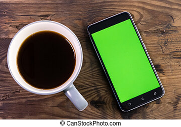 Smart phone with green screen next to coffee cup