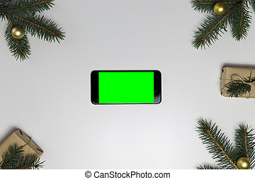 Smart phone with green screen surrounded by Christmas decorations. Holiday and christmas concept. Wrapped christmas gifts.