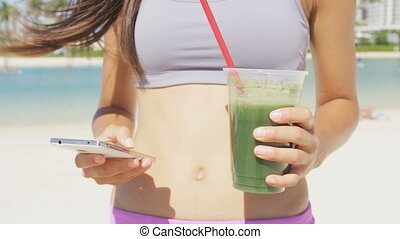 Smart phone woman drinking vegetable Green detox smoothie - ...
