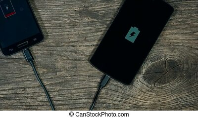 smart phones charging on grunge wood background. Status on screen.