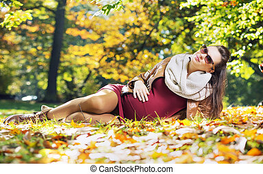Smart pregnant woman in the autumn park