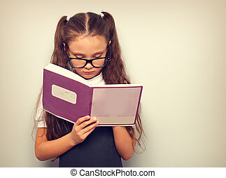 Smart pupil kid girl in eyeglasses looking in the textbook and dooing the exercices