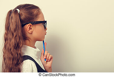 Smart pupil kid girl in eyeglasses looking on the wall background with drawing pencil and thinking about