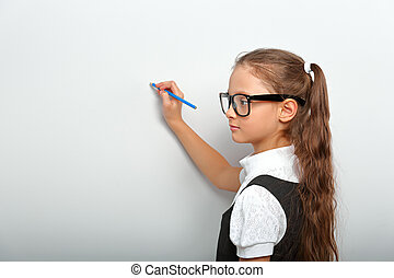 Smart pupil kid girl in eyeglasses looking on the wall background with drawing pencil