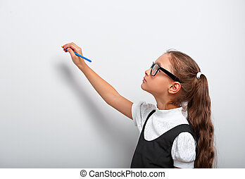 Smart pupil kid girl in eyeglasses looking up on the blue wall background with drawing pencil