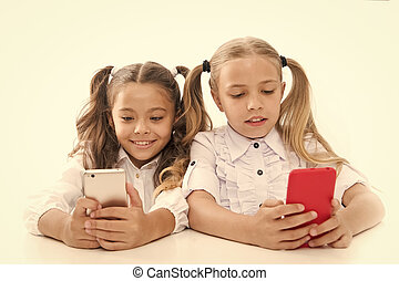 Smart pupils. Little pupils texting message during class isolated on white. Cute lyceum pupils diving deep into smartphone lessons. Small pupils using mobile phones in classroom.