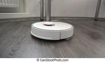 Smart robotic vacuum cleaner cleans the laminate floor. -...