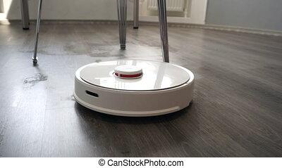 Smart robotic vacuum cleaner in action. Wet floor cleaning.