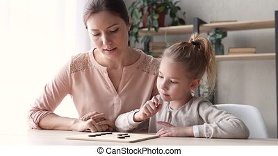 Smart school girl playing draughts with babysitter or mother. Cute small kid daughter concentrating learning board game leisure activity. Young mom teaching child thinking of checkers strategy concept