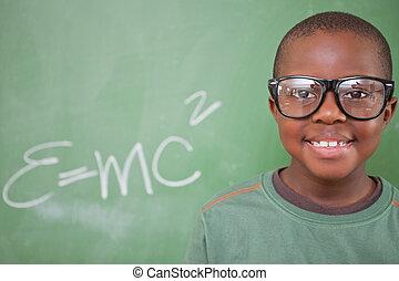 Smart schoolboy posing in front of a blackboard