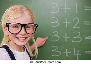 Smart schoolgirl pointing at something on a blackboard